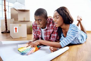 young African couple having fun deciding on paint color swatch for new home apartment