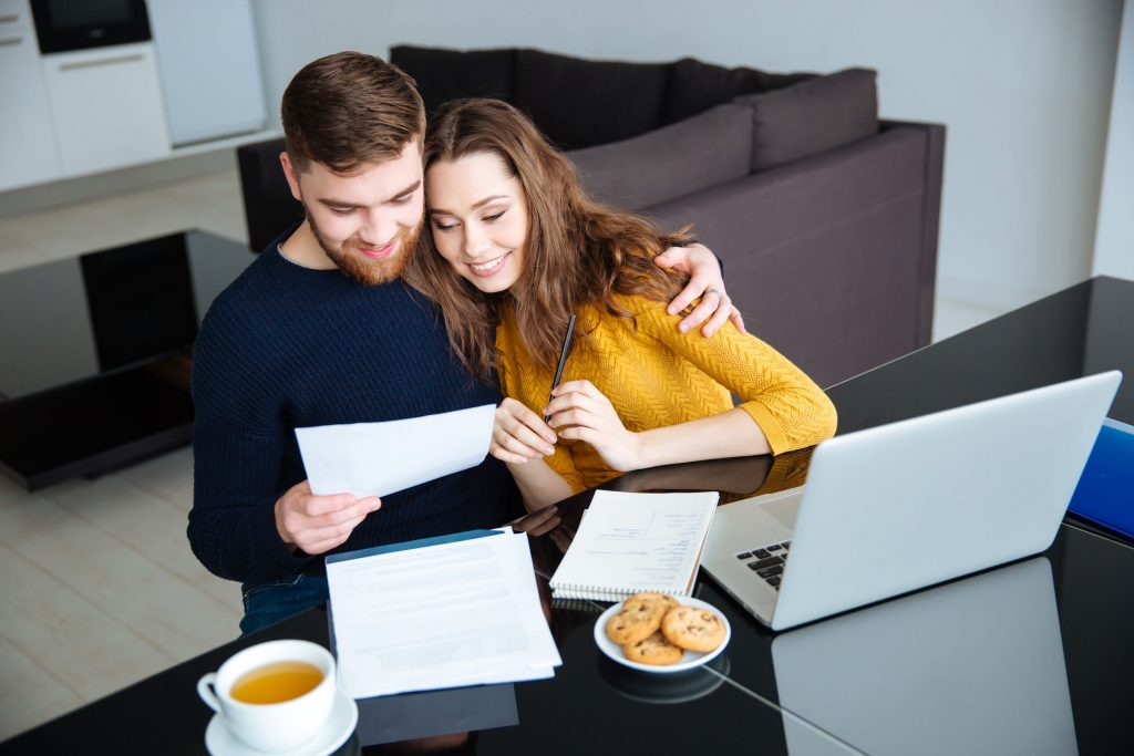 Smiling young couple applying for a mortgage at home
