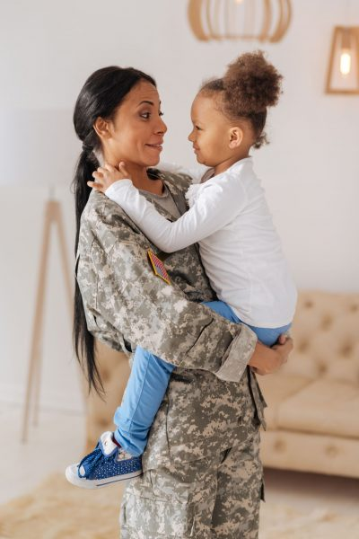 Female Military Mom holding Child excited about VA Loan for new home